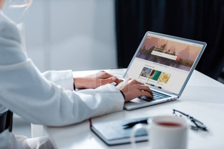 cropped view of woman using laptop with shutterstock website on screen at office desk