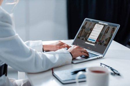 Photo pour Vue recadrée de la femme à l'aide d'un ordinateur portable avec le site linkedin à l'écran au bureau - image libre de droit