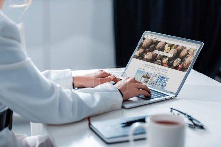 Photo pour Vue recadrée de femme avec ordinateur portable depositphotos site sur écran au bureau - image libre de droit