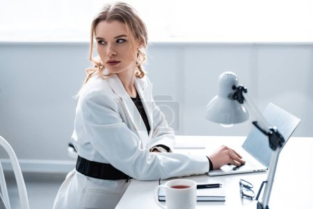 Photo for Beautiful businesswoman in formal wear sitting at desk and looking away while using laptop at workplace - Royalty Free Image