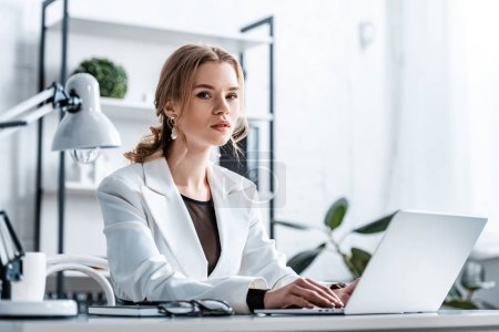 Photo for Serious businesswoman in formal wear sitting at desk, looking at camera and typing on laptop at workplace - Royalty Free Image