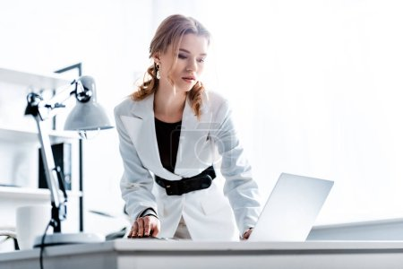 Photo for Concentrated businesswoman in formal wear using laptop at workplace - Royalty Free Image
