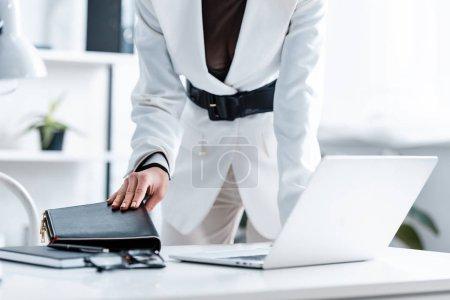 Photo pour Vue recadrée de femme d'affaires dans l'usure formelle tenant carnet au bureau de l'ordinateur - image libre de droit
