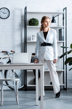 stylish businesswoman in white formal wear in modern office interior