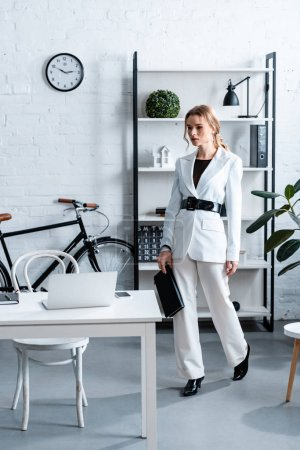 serious businesswoman in white formal wear holding notebook in modern office interior