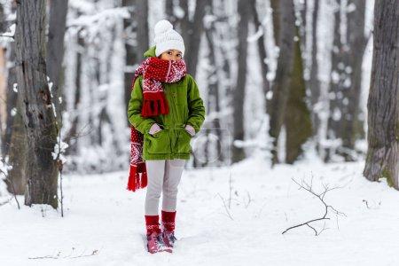 Photo pour Enfant afro-américain dans des vêtements chauds avec les mains dans les poches en regardant la caméra à winter park - image libre de droit