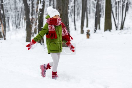 Photo for African american child in warm clothing walking and looking at camera in winter park - Royalty Free Image
