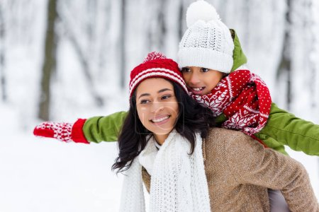 beautiful african american woman giving piggyback ride to cheerful daughter in winter park