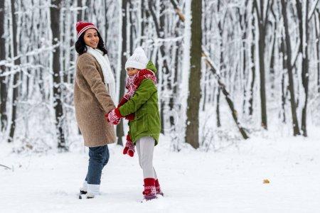 Photo pour Afro-américaine mère et fille, souriant, main dans la main et en regardant la caméra à winter park - image libre de droit
