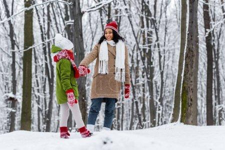 Photo pour Afro-américaine et preteen fille marche, main dans la main et l'autre en regardant à winter park - image libre de droit