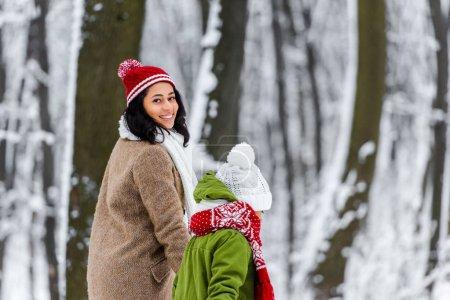 Photo pour Souriante mère afro-américaine promenait avec fille et regardant la caméra à winter park - image libre de droit