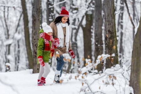 Photo pour Femme afro-américaine joyeuse marche avec preteen fille à winter park - image libre de droit