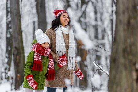 Photo pour Séduisante mère afro-américaine et preteen fille souriante et marcher dans le parc d'hiver - image libre de droit