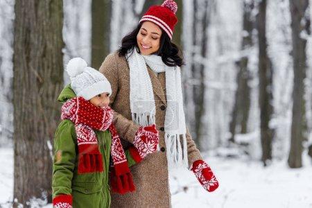 Photo pour Belle femme afro-américaine en regardant les enfants préados mignon et souriant à winter park - image libre de droit