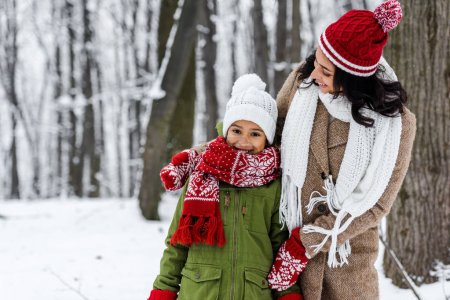 attractive african american mom hugging cheerful daughter in winter park
