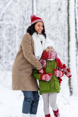 Photo pour Joyeux afro-américain maman avec les yeux fermés étreignant fille préadolescente dans le parc d'hiver - image libre de droit