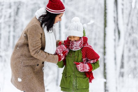 Photo for Smiling african american mom hugging preteen daughter with closed eyes during snowfall in winter park - Royalty Free Image