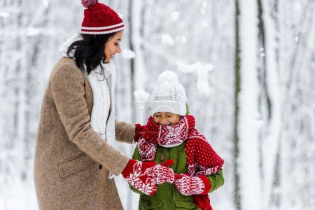 Photo pour Joyeuse maman afro-américaine étreignant mignon enfant avec les yeux fermés pendant les chutes de neige dans le parc d'hiver - image libre de droit
