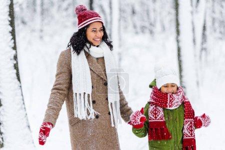 Photo pour Joyeuse maman afro-américaine et mignon enfant debout pendant les chutes de neige dans le parc d'hiver - image libre de droit