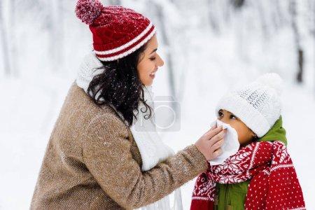 Photo pour Belle femme afro-américaine, essuyant avec nez de serviette de preteen fille à winter park - image libre de droit