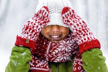 Photo pour Mignon enfant afro-américain avec chapeau tricoté tiré sur les yeux souriant pendant les chutes de neige - image libre de droit