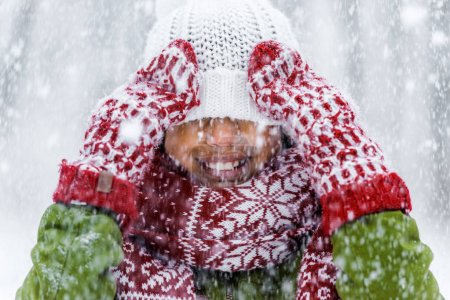 close up view of smiling african american child with knitted hat pulled over eyes during snowfall