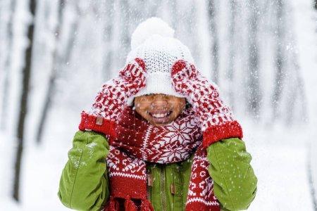 Photo pour Enfant afro-américain souriant avec chapeau tricoté tiré sur les yeux pendant les chutes de neige dans le parc d'hiver - image libre de droit