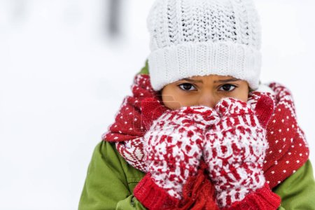 Photo for Close up view of african american child in knitted hat, mittens and scarf looking at camera in winter - Royalty Free Image