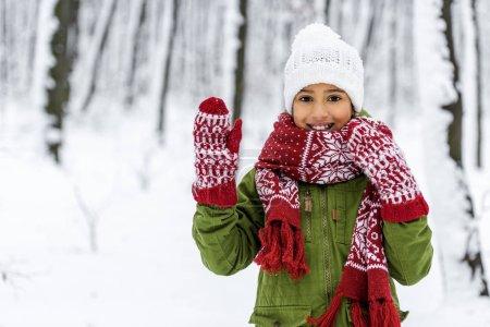 Photo pour Enfants afro-américains dans des vêtements chauds, souriant, agitant à la main et en regardant la caméra à winter park - image libre de droit
