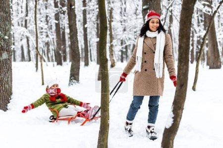 Photo pour Belle femme afro-américaine souriant et tirant preteen fille dans des vêtements chauds sur luge à winter park - image libre de droit