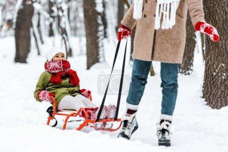 Photo pour Recadrée vue de mère tirant fille dans des vêtements chauds sur luge à winter park - image libre de droit