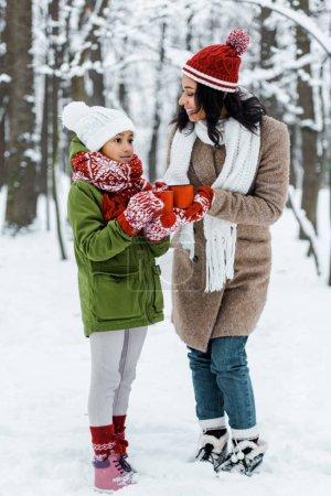 Photo pour Séduisante mère afro-américaine et mignonne fille parler les uns aux autres et tenant des tasses de thé dans la forêt enneigée - image libre de droit