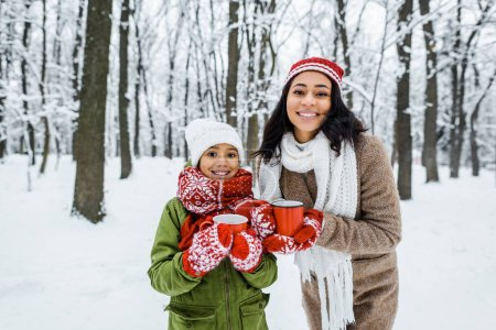 attractive african american mother and cute daughter holding cups of tea and smiling while looking at camera in snowy forest