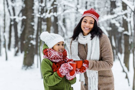 attractive african american mother and cute daughter holding red cups of tea and staying near trees in snowy forest