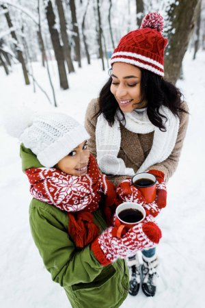 attractive african american mother and cute daughter holding red cups of tea while staying near trees in snowy forest