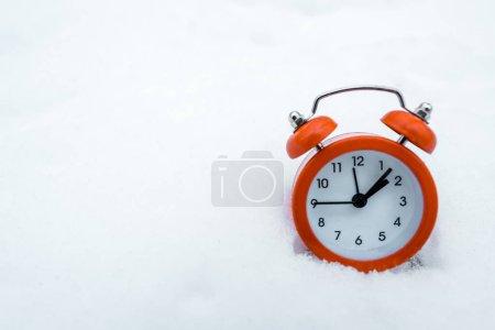 Photo pour Réveil rétro rouge debout sur la neige blanche près des arbres dans la forêt enneigée - image libre de droit