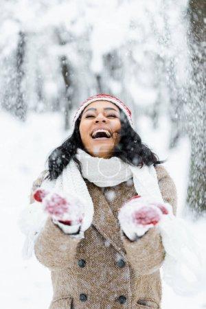 Foto de Atractiva mujer afroamericana lanzando nieve y sonriendo en bosque del invierno - Imagen libre de derechos