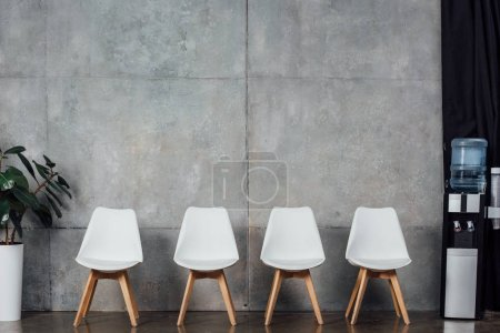 Photo for Modern white chairs in waiting hall with plant and water cooler - Royalty Free Image