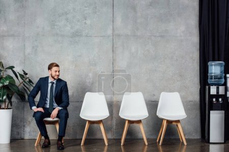 Photo for Stylish handsome businessman in suit sitting in waiting hall - Royalty Free Image