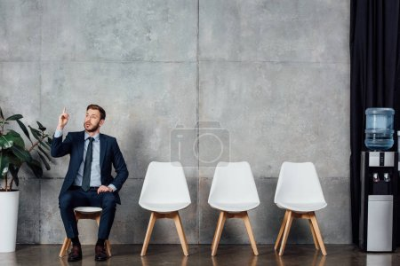 businessman in suit showing idea gesture and sitting in waiting hall