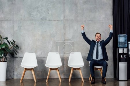excited businessman sitting on chair and cheering with clenched fists in waiting hall