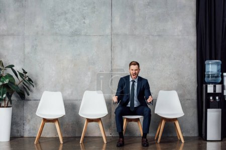 businessman sitting on chair and cheering with clenched fists in waiting hall