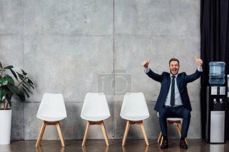 Foto de Emocionado el empresario en traje sentado y mostrando los pulgares para arriba en sala de espera - Imagen libre de derechos