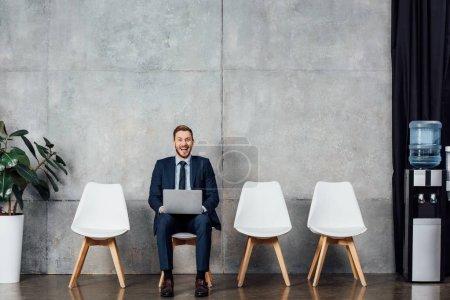 Photo pour Homme d'affaires joyeux assis sur la chaise et en utilisant un ordinateur portable dans la salle d'attente - image libre de droit