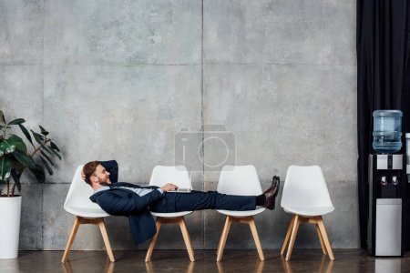 Photo for Smiling businessman lying on chairs and using laptop in waiting hall - Royalty Free Image