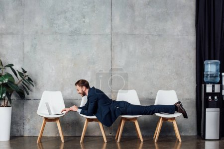 Photo for Businessman lying on chairs and using laptop in waiting hall - Royalty Free Image