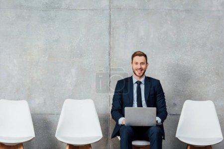 Photo pour Homme d'affaires souriant assis sur une chaise et utilisant un ordinateur portable dans la salle d'attente - image libre de droit