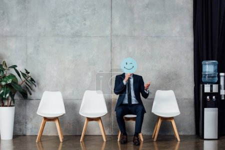 Photo for Businessman in suit sitting on chair and holding card with winking face expression in waiting hall - Royalty Free Image