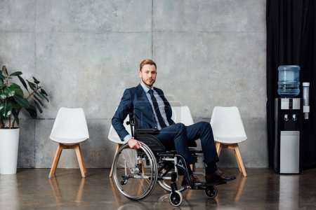 serious businessman sitting in wheelchair in waiting hall and looking at camera