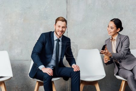 handsome smiling businessman looking at camera while asian businesswoman holding smartphone in waiting hall